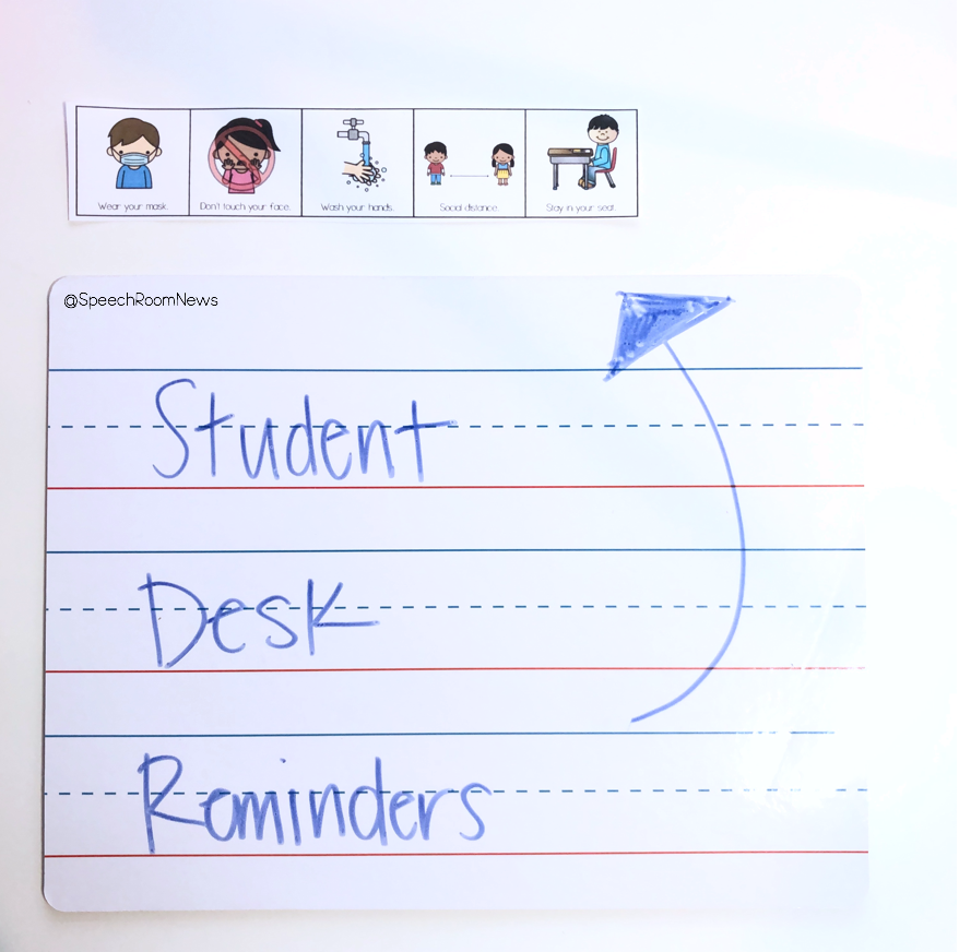 A picture of a student desk with a strip of COVID safety reminders.